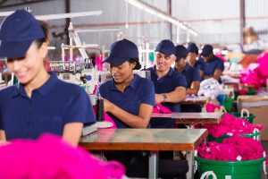 "group multiracial factory workers sewing in clothing factory to illustrate ""labor costs"""