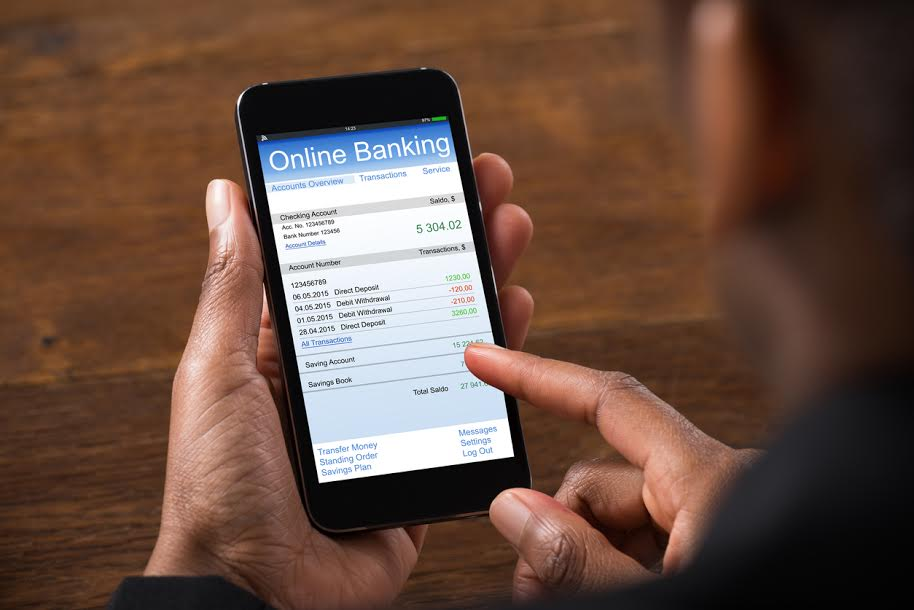 Hand Using Online Banking and Online Business Bank Account On Mobile Phone