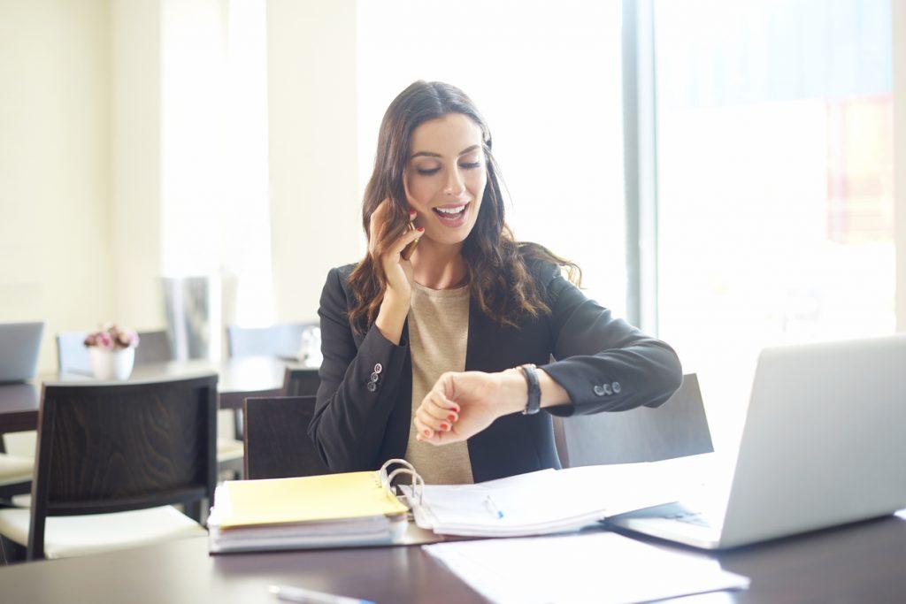 """Mujer de negocios hablando por celular y mirando su reloj para expresar la idea """"gestión de tiempo"""""""
