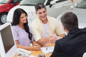 "Smiling salesman shaking a customer hand at new car showroom to show concept of ""sales funnel"""