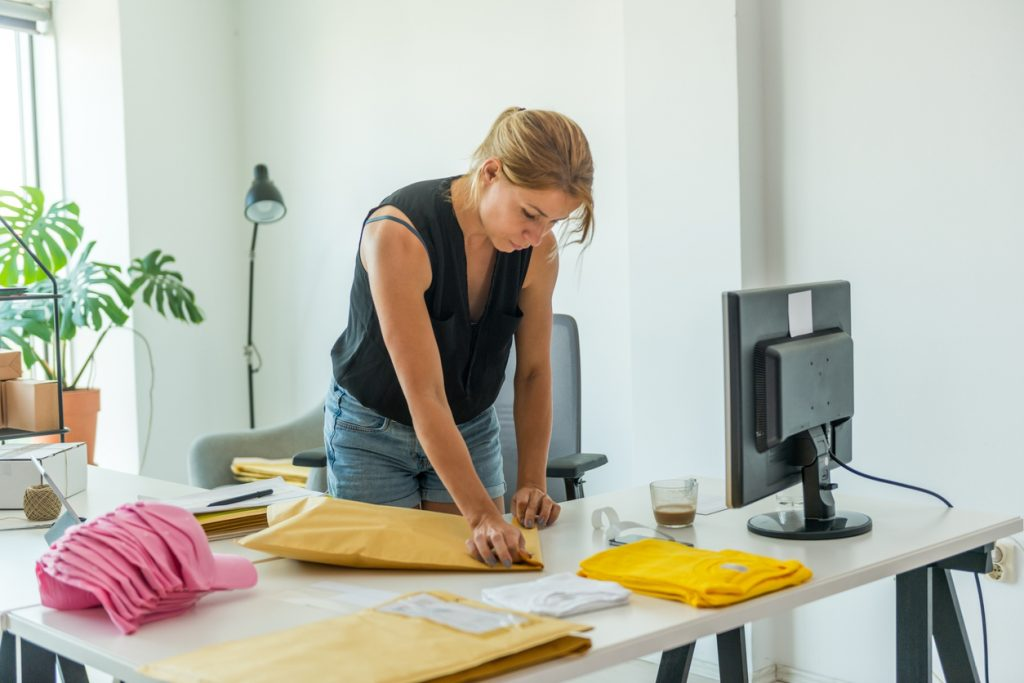 Woman working from home packing merchandise into envelopes to show how to make money online