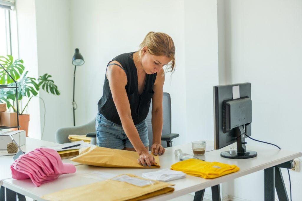 Mujer trabajando en casa empaquetando ropa en sobres para enviar, para mostrar cómo ganar dinero en línea