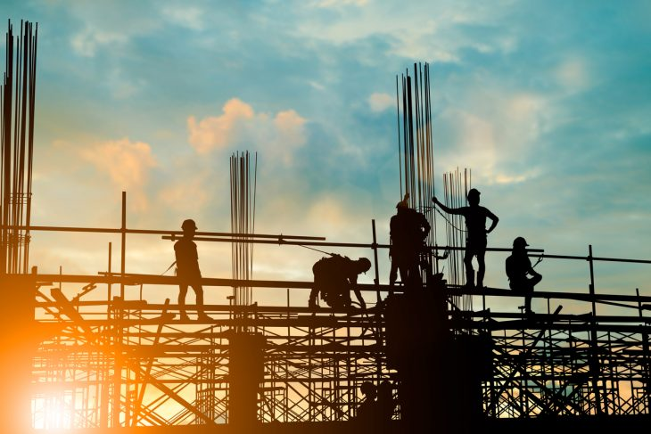 Silhouette of engineer and construction team of construction business working safely on scaffolding on high rise building. over blurred background sunset pastel for industry background with light fair