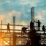 Siluetas de equipo de empresa de construcción trabajando sobre andamios de una obra al atardecer