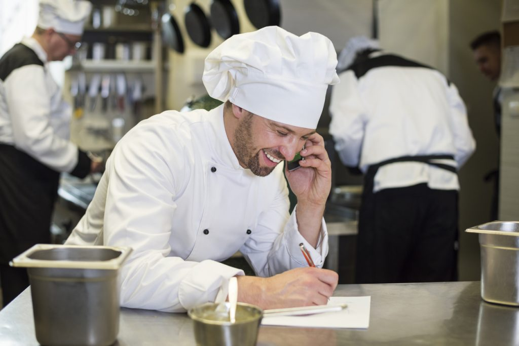 Chef in restaurant kitchen on the phone making an order from supplier and smiling
