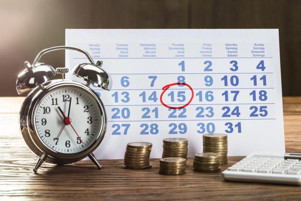 Reloj, montones de monedas y calendario señalando el día de un pago, para ilustrar la idea de eliminar una deuda de tu reporte de crédito