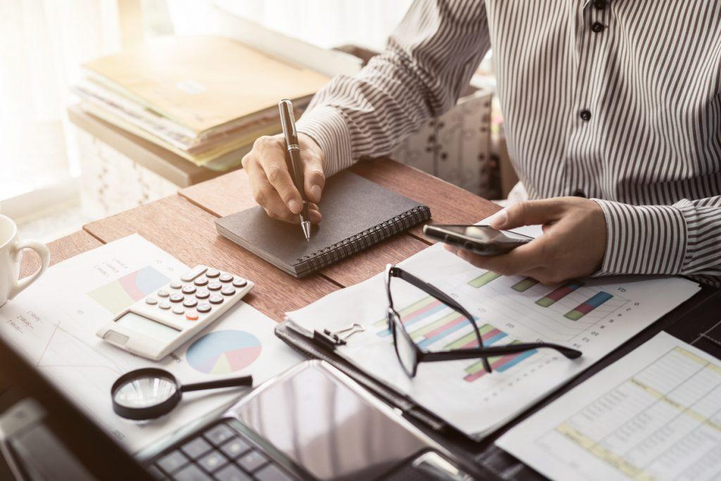 """Escritorio de hombre de negocios con papeleo y calculadora para ilustrar la idea de """"buro de credito"""""""