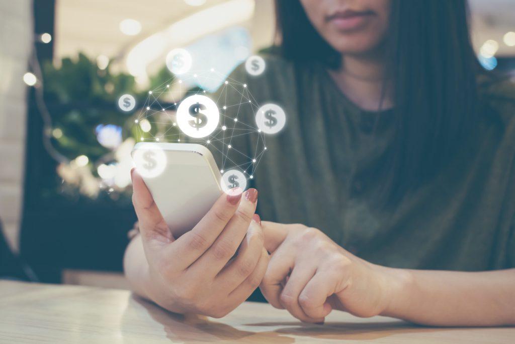 Mujer usando calculadora y signos de dólar flotando en el aire. Concepto: puntaje de crédito y tasa de interes.