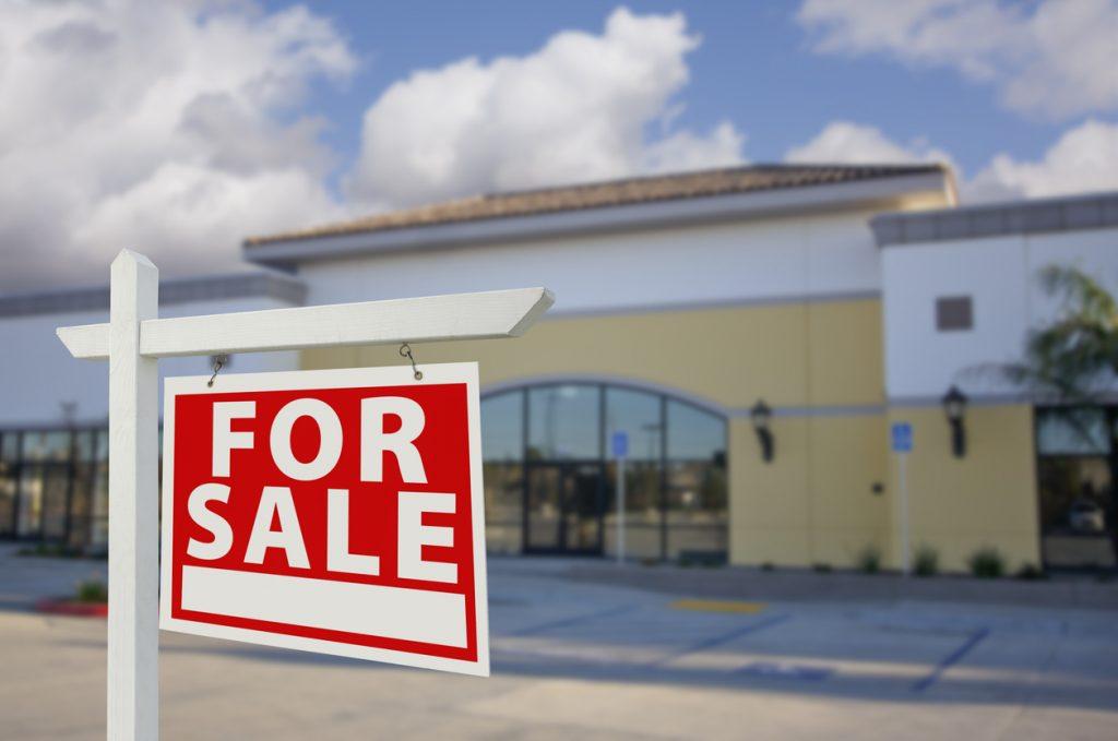 """Cartel de """"Se vende"""" (""""For Sale"""") frente a espacio comercial. Concepto: como comenzar un negocio."""