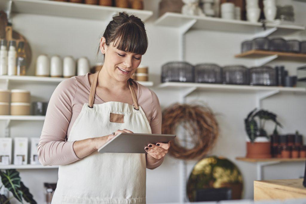 Dueña de floristería en su negocio consultando credito en tableta. Concepto: cómo construir credito comercial.