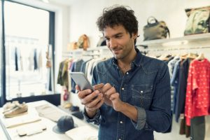 Business owner using smart phone in clothing store. Concept: online bank account.