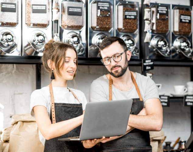 Couple of coffee store owners reading on laptop standing at the counter of the shop. Concept: how to read your credit report.