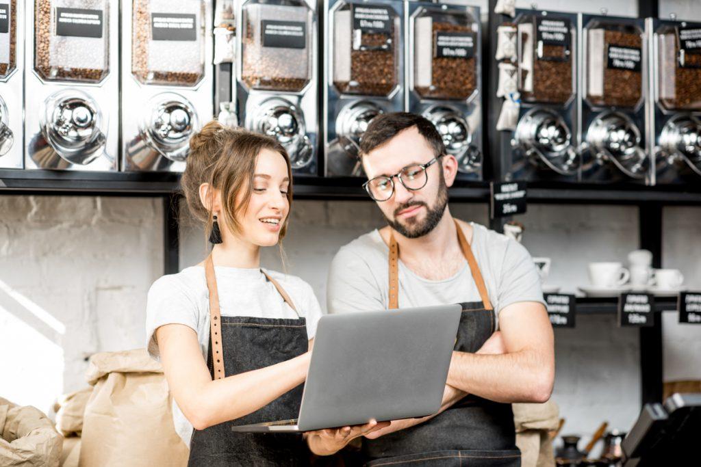 Pareja de dueños de tienda de café en el mostrador, leyendo en un laptop. Concepto: cómo leer tu reporte de credito.