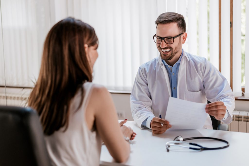 Happy male doctor discussing with patient at table in clinic. Concept: healt insurance options