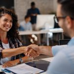 Young woman signing contracts and handshake with a manager. Concept: good credit score.
