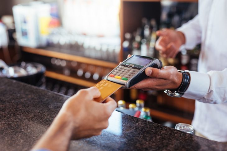 Customer making payment using credit card. Close up of card payment being made between customer and bartender in cafe. Concept: How to avoid identity theft