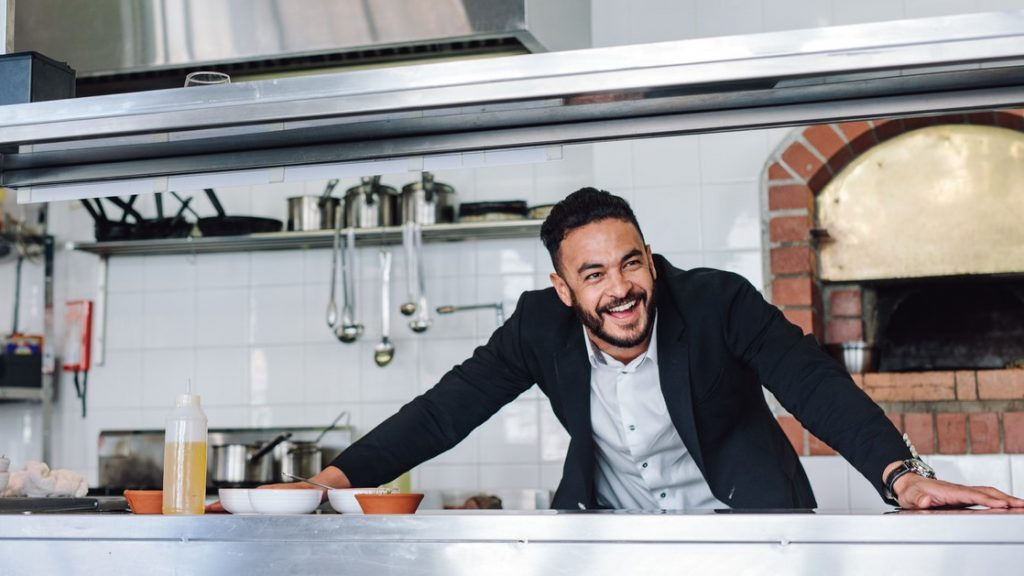Happy young restaurant owner standing at kitchen counter looking away and smiling. Caucasian businessman in commercial kitchen. concept: good credit score