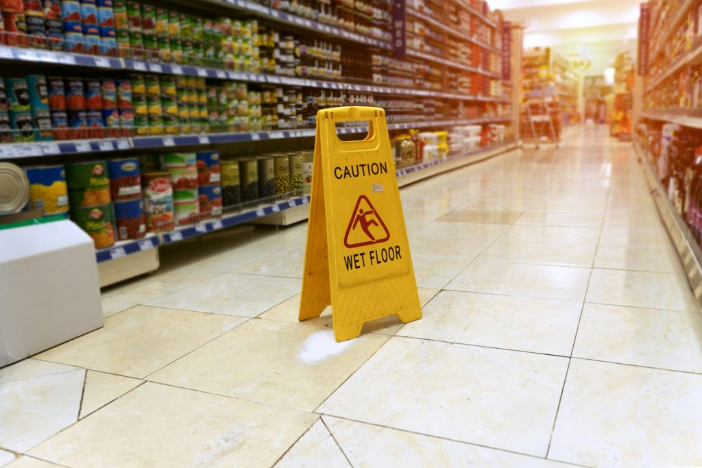 Yellow sign - caution. Wet floor is in the supermarket against the background of blurry products standing on the shelves. Concept: business lawsuit.