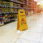 """Señal amarilla de """"¡Cuidado! Piso mojado"""" en el pasillo de un supermercado. Concepto: demanda laboral."""