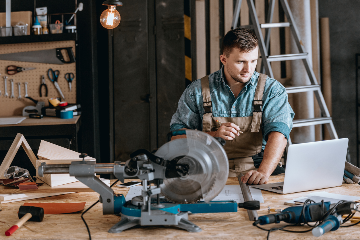 Young bearded carpenter focused on planning woodworking project using laptop in workshop. Concept: best laptops for business