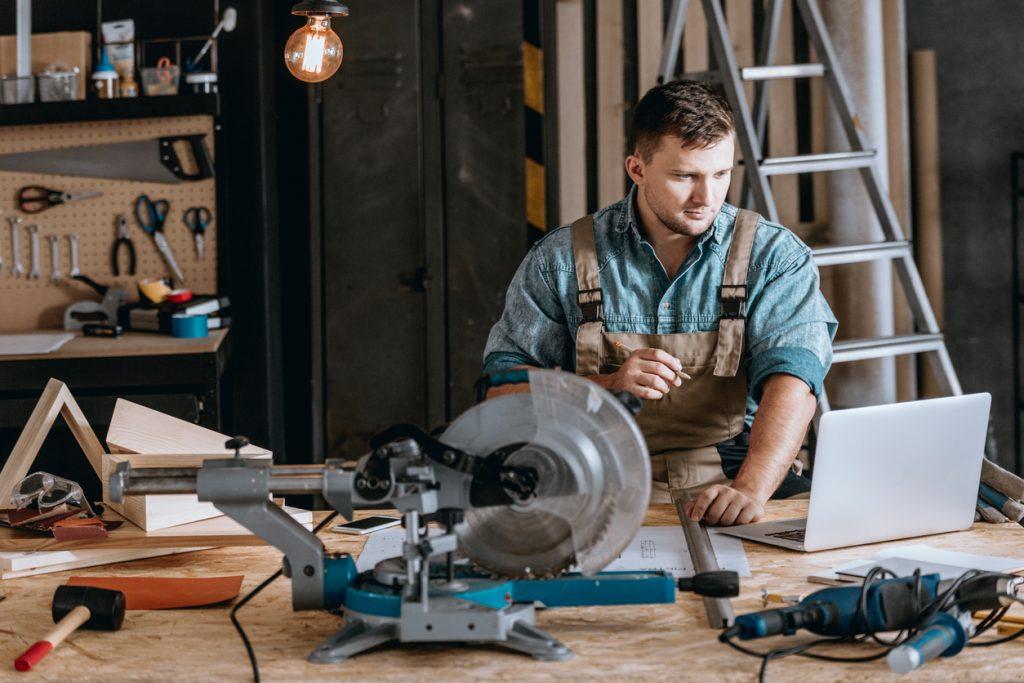 Carpintero en su taller, en mesa de trabajo con instrumental de carpinteriá y usando un laptop. Concepto: los mejores laptops para tu negocio.