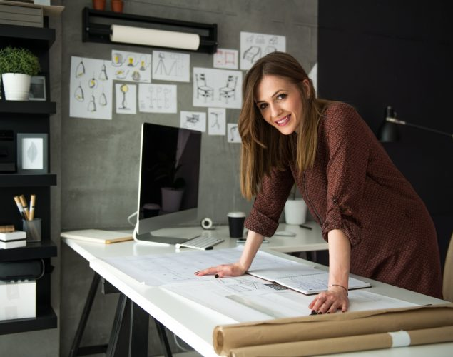 Smiling designer in her studio's desk working on her designs. Concept: grow you business