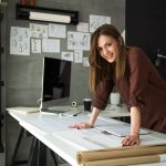 Joven diseñadora en el escritorio de su estudio frente a sus diseños. Comcepto: prestamos para negocios