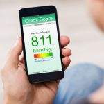 Man Holding Smart Phone Showing Credit Score Application On A Screen. Concept: how to use Credit Karma.