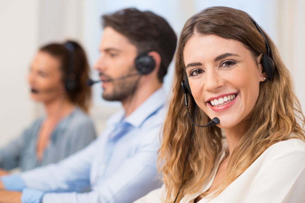 Smiling female call centre operator doing her job with a headset while looking at the camera. Portrait of happy woman in a call center smiling and working. Portrait of happy smiling female customer support phone operator at workplace. Concept: customer database