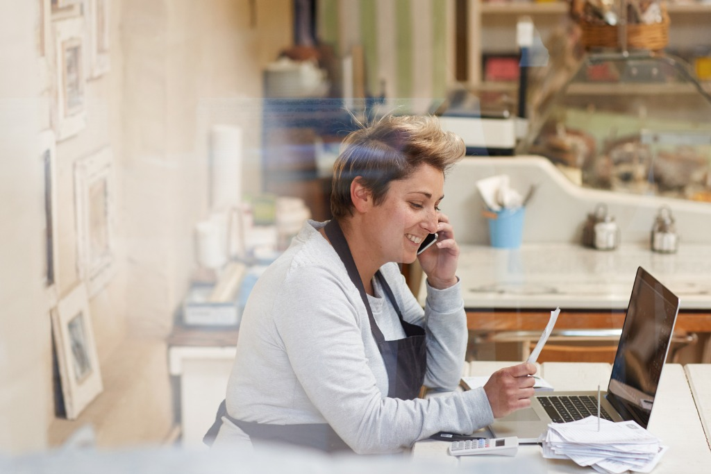Female business owner with apron on computer and making calls negotiating her high interet rates on a business loan.