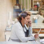 Dueña de un negocio sentada frente a la computadora y haciendo una llamada de teléfono. Concepto: altos intereses.