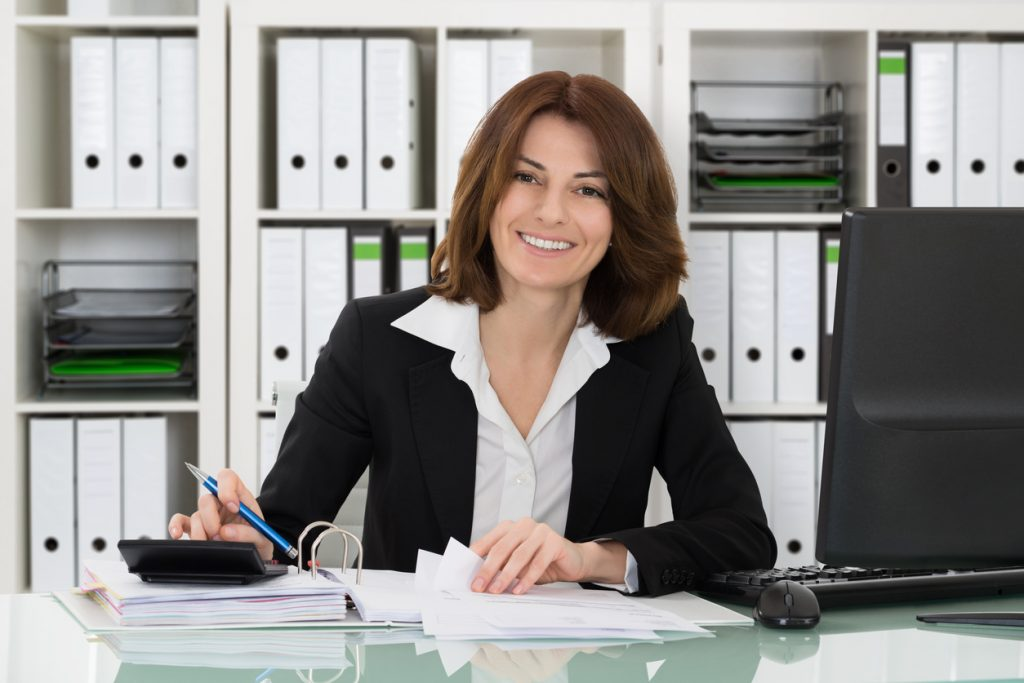 Happy female accountant Calculating Tax At Desk In Office. Concept: grow your accounting firm with a business loan