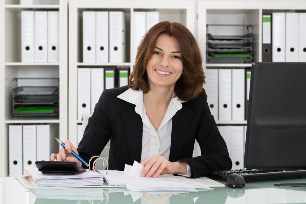 Mujer contable realizando inpuestos sentada en el escritorio en su oficina. Cómo hacer crecer tu empresa de contabilidad con un préstamo comercial