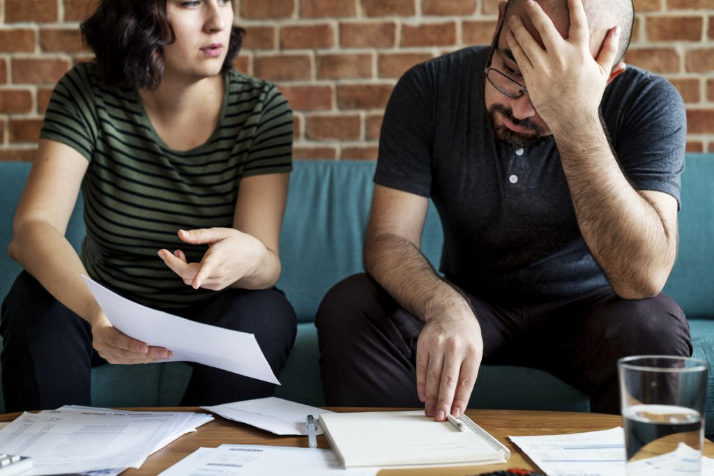 Worried couple on couch with paperwork managing debt. Concept: pay off debt