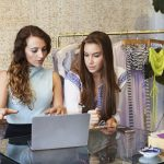 Two young women working on clothig store analyzing information on laptop. Concept: Busines Loan Interest Rates