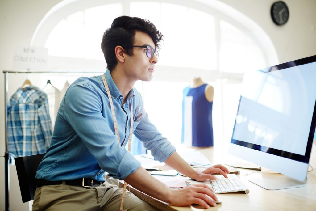 Young creative fashion designer sitting in front of computer and searching in the net. Concept: business loan refinancing