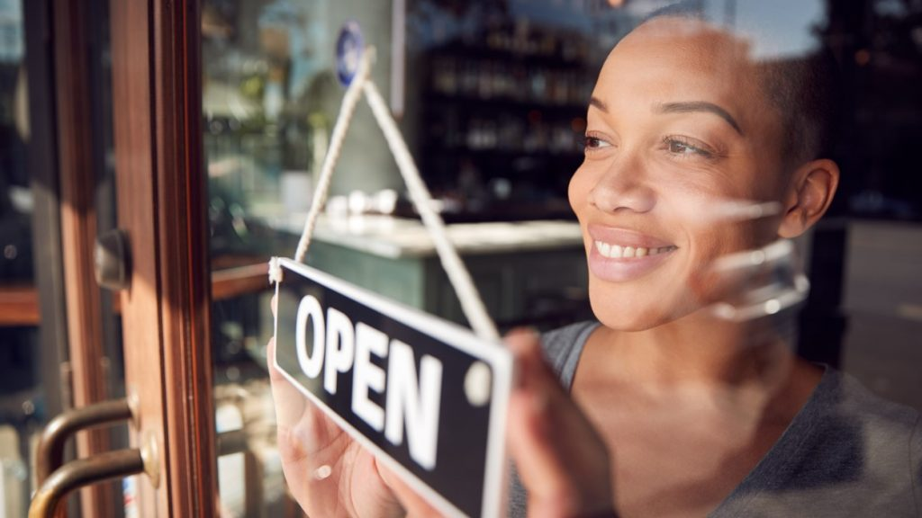Female Owner Of Start Up Coffee Shop Or Restaurant Turning Round Open Sign On Door. concept: business loan requirements