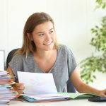 Joven empresaria sonriente sentada frente a computadora y organizando documentos. Concepto: Requisitos para un préstamo: lista de documentos.