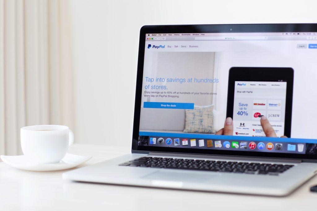 Laptop sobre escritorio mostrando página principal de PayPal. Concepto: cómo usar PayPal en tu negocio