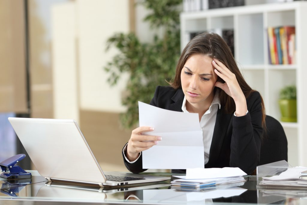 Worried businesswoman reading a notification sitting in a desktop at office. Concept: business loan declined