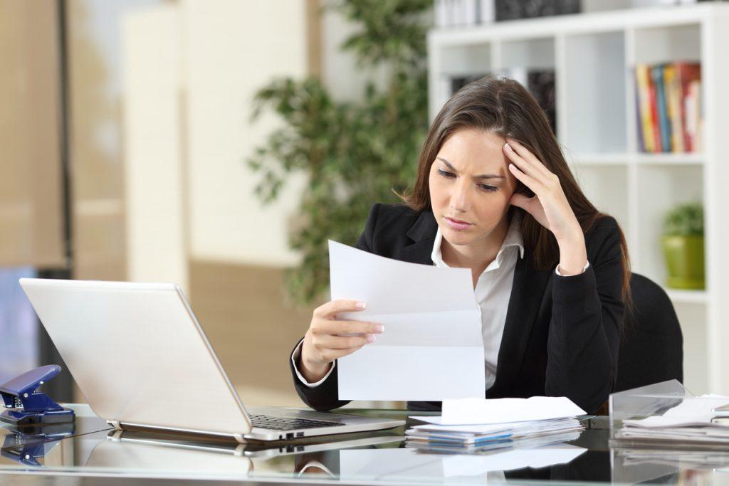 Empresaria leyendo solicitud de pre´stamo rechazada sentada el escritorio de su oficina.