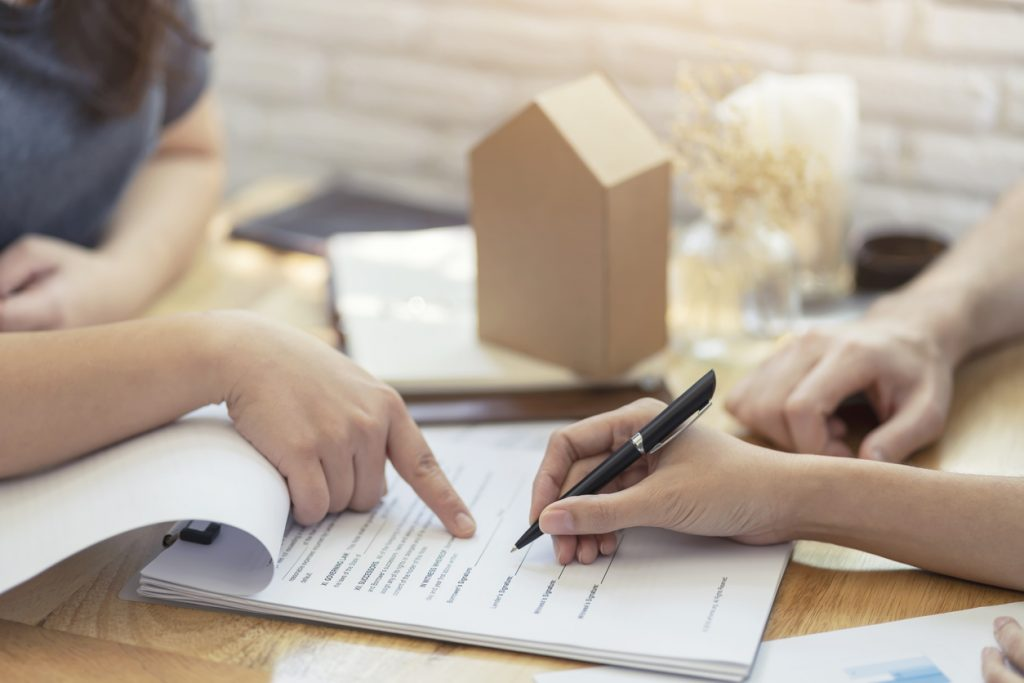 woman putting signature on document contract, real estate purchase, success business contract deals with sale represent. Concept: personal loan for business.