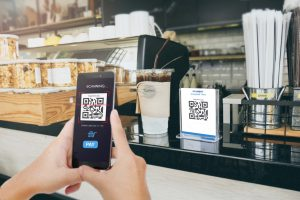 Man scaning tag in Coffee shop accepted generate digital pay without money. Concept: PayPal