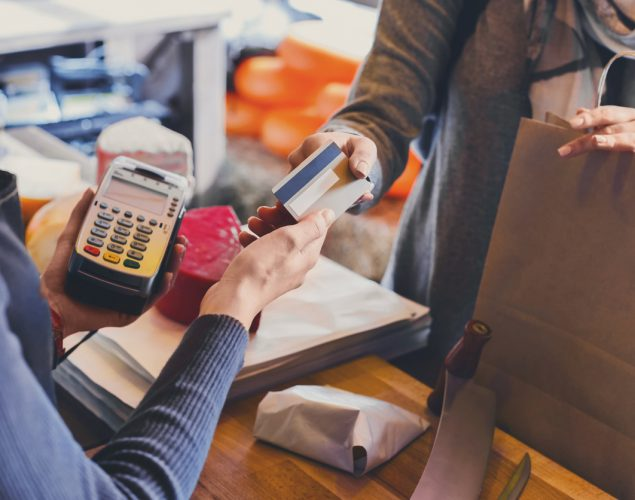 Customer paying for order in grocery shop using a credit card while cashier is using a credit card reader. Concept: merchant cash advance
