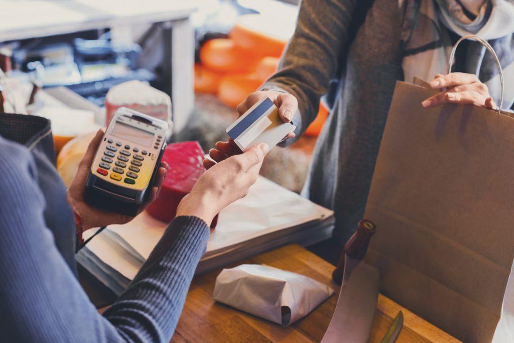 Cliente pagando en tienda de comestibles con tarjeta de crédito; dependiente usando lector de tarjeta de crédito. Concepto: adelantos de efectivo.
