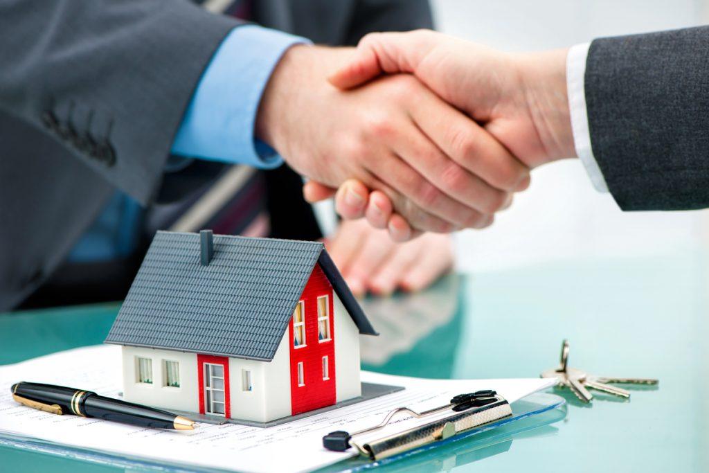 Mano de prestamista hipotecario estrechando mano de prestatario sobre contrato de hipoteca y una casa en miniatura. Concepto: diferencia entre hipoteca y préstamo