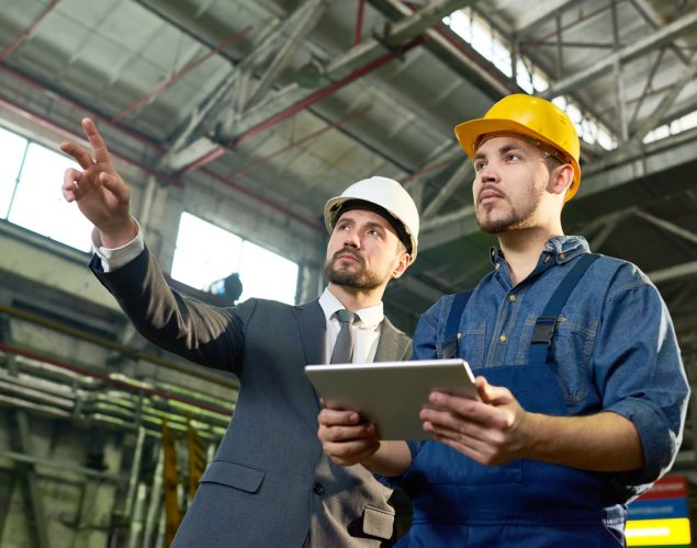Businessman pointing up while discussing some future plans with factory worker holding digital tablet. Concept: how much to invest