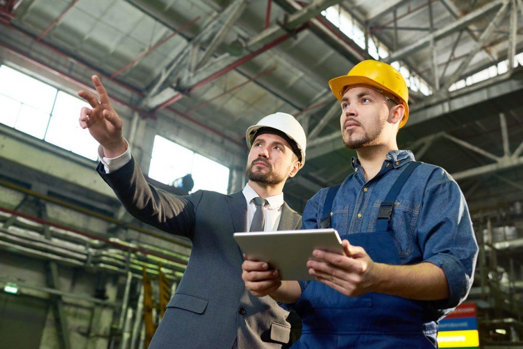 Dueño de empresa señalando algo y haciendo planes con trabajador en una fábrica- Concepto: cuánto invertir.
