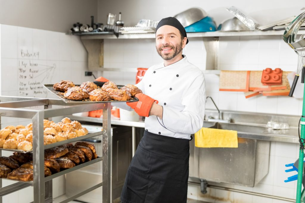 Dueño de un pequeño negocio (panadero) sonriente y mostrando una bandeja de dulces recién horneados. Concepto: microcrédito.