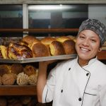 Smiling immigrant business owner (bakery) carrying a tray of fresh baked goods. Concept: loans for immigrants